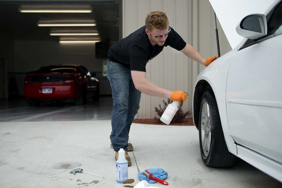 AutoLux Custom Car Care owner Jimmy Sheets cleans the rims on a customer's car. The auto detailing service shop at 5708 W. Wackerly is having its grand opening today. Photo: Brittney Lohmiller | Blohmiller@mdn.net