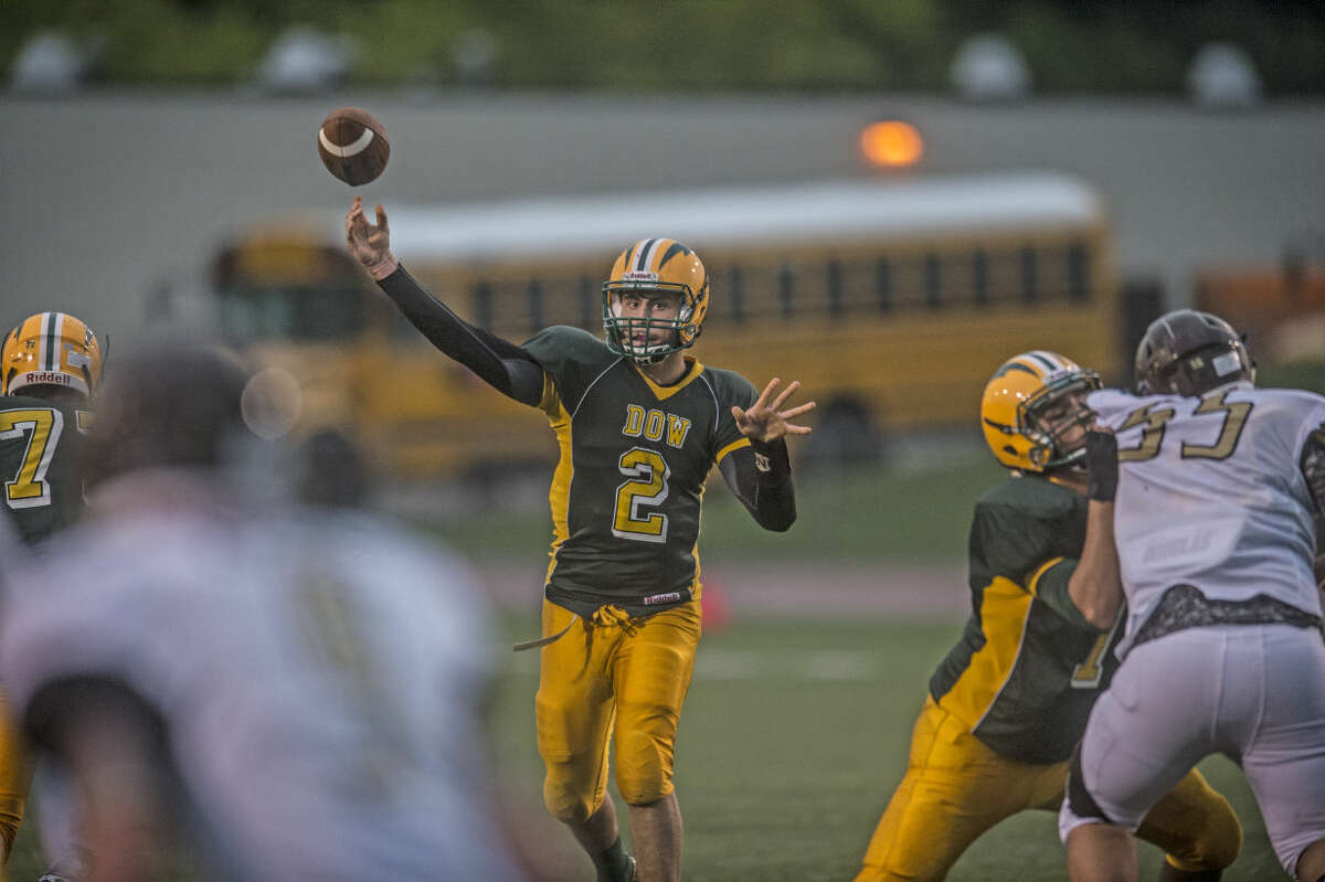 Dow High junior quarterback Bruce Mann throws the ball in the first quarter of the game against Bay City Western on Thursday at Midland Community Stadium.