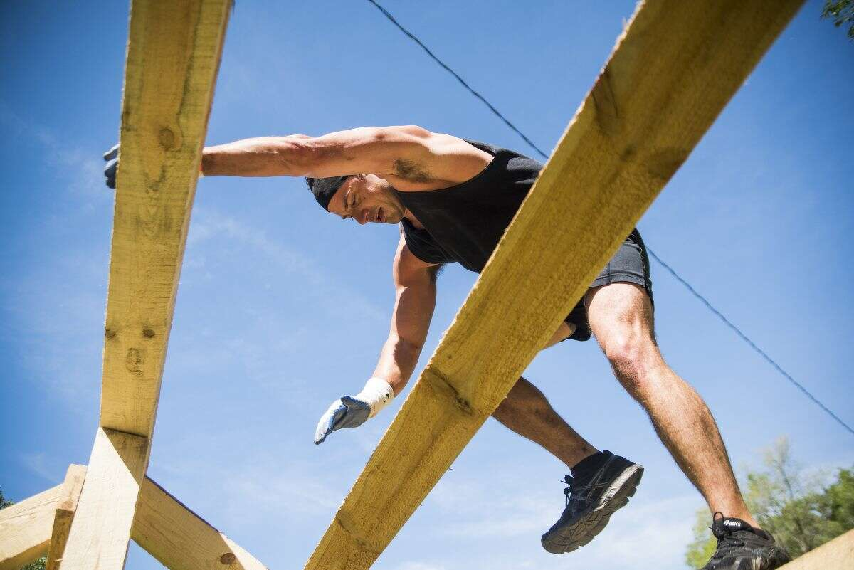Pete Shepherd of Midland climbs down from an obstacle during the Forest Frenzy race and obstacle course on Saturday at the Midland City Forest.