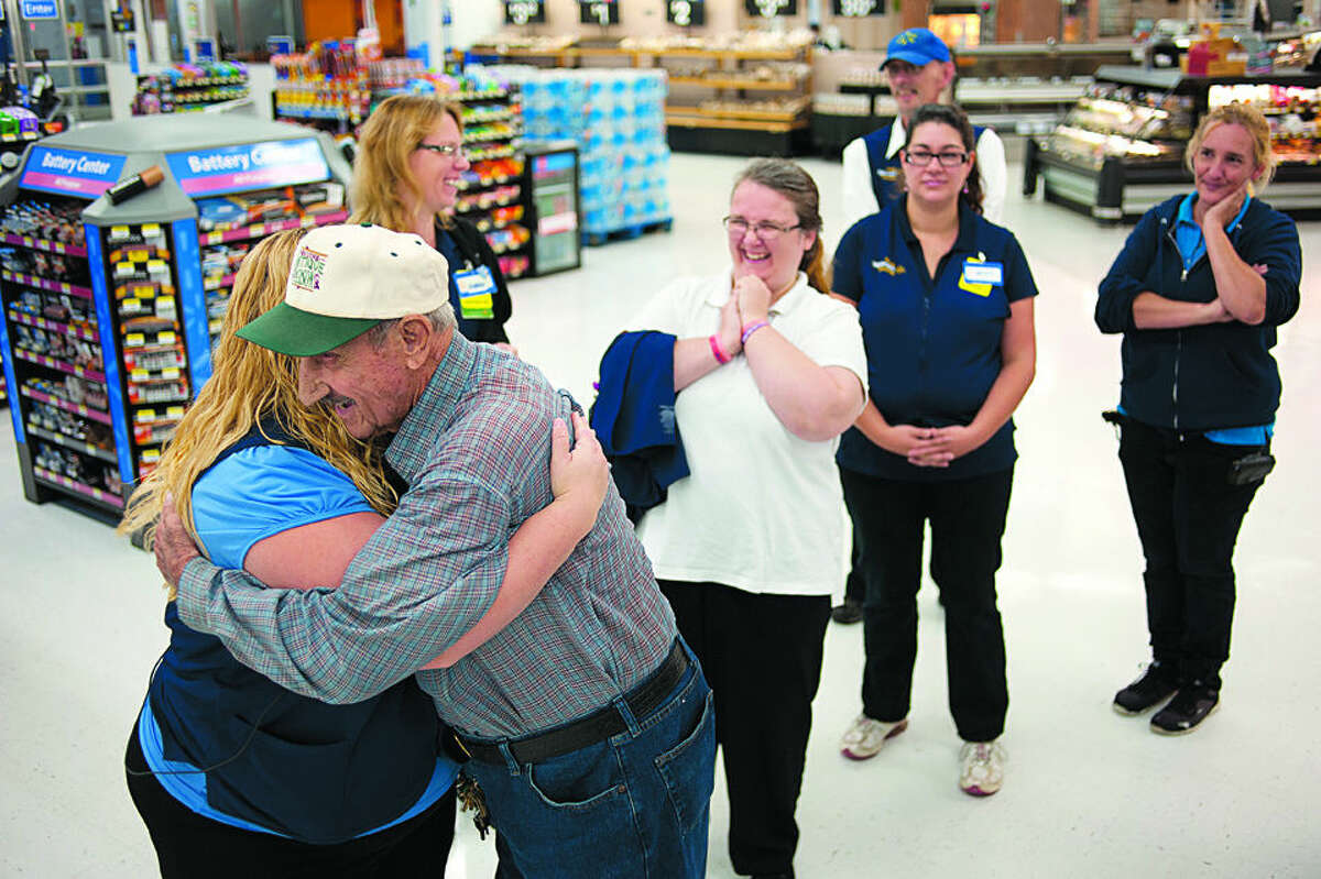 BRITTNEY LOHMILLER | blohmiller@mdn.net Walmart employee Malissa Gillespie, left, gives Cecil Rydman of Beaverton a hug and wished him a happy birthday Friday morning. Walmart employees gathered inside the Midland store to celebrate Cecil's upcoming 100th birthday by giving him a card and cake. Rydman has been shopping at the store since its' opening.