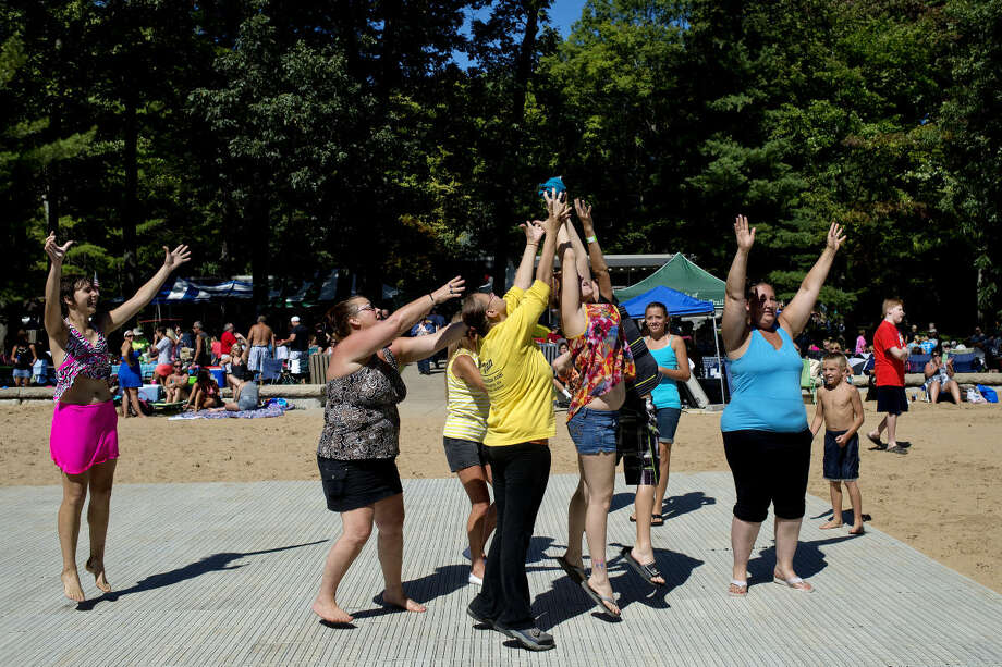 Patrons on the dance floor reach for a free T-shirt that was thrown in the air by a staff member during Parkapalooza last year at Sanford Lake Park. Jimmy & The Gowlers were performing at the time. This year's event is planned for Sunday. Photo: Nick King | Midland  Daily News