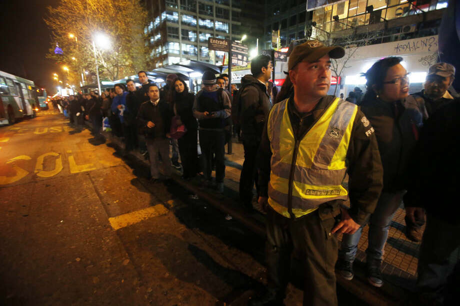 A police officer stands in the street to direct traffic as people stand in a line for public transportation after an earthquake in Santiago, Chile, Wednesday, Sept. 16, 2015. A powerful magnitude-8.3 earthquake hit off Chile's northern coast Wednesday night, causing buildings to sway in Santiago and other cities and sending people running into the streets. (AP Photo/Luis Hidalgo) Photo: Luis Hidalgo