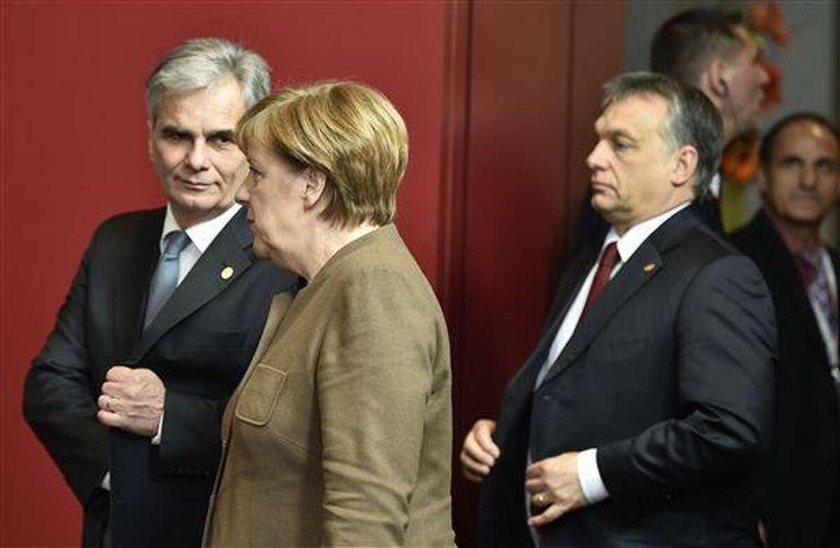 La canciller alemana Angela Merkel conversa con el canciller austriaco Werner Faymann durante una fotografía de grupo en una cumbre de la Unión Europea, el jueves 18 de febrero de 2016, en Bruselas, Bélgica. (Foto AP/Martin Meissner)