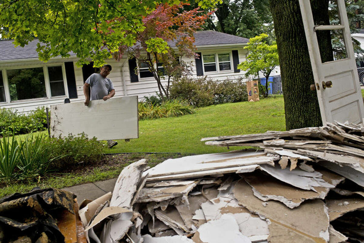 Contractor John Long carries scrap wood outside of a house that Sanford residents Colette and Philip Urian of Fox Run Properties are flipping.