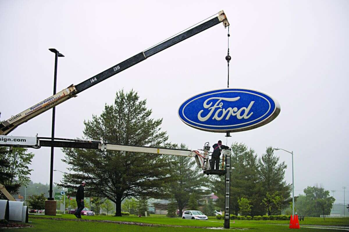 NEIL BLAKE   nblake@mdn.net The sign from Midland Ford-Lincoln is moved to the business' new location on Joe Mann Boulevard on Friday by Higher Image Design.