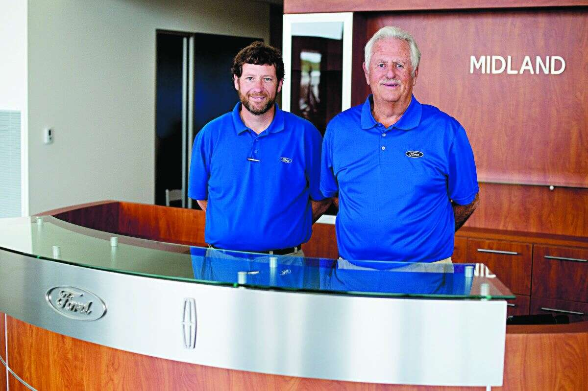 NEIL BLAKE   nblake@mdn.net Chad Wilson, left, and his father Joe Wilson stand in the new Midland Ford-Lincoln building on Joe Mann Boulevard. The business is moving from its current location at 1303 S. Saginaw.