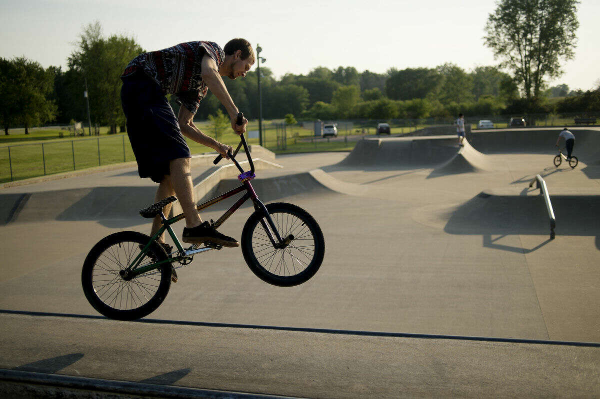 """Parker Norton of Midland works on his BMX bike before riding at Trilogy Skatepark in Midland on Wednesday. """"We can ride without getting shut down,"""" Norton said. The Midland Parks and Recreation Commission has approved use of bikes in the park."""
