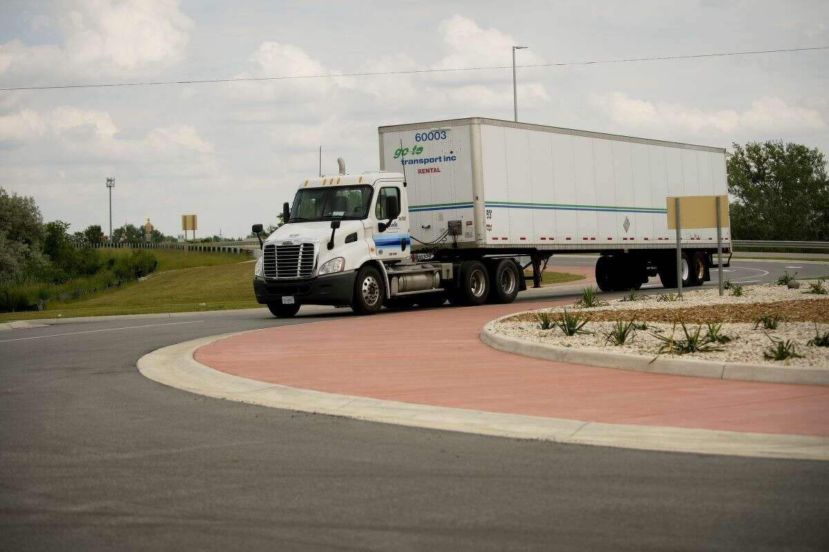A semi truck navigates the roundabout on M-20/U.S.-10 Business Route at the Patrick Road crossover in this Daily News file photo.