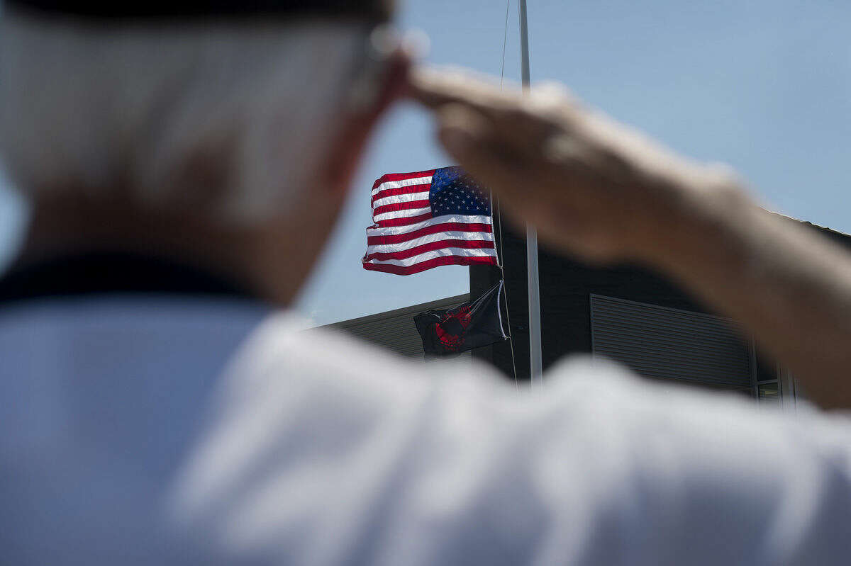 Bob Fahlsing of Midland salutes the American and POW/MIA flags as they are raised outside of McDonald Ford in Freeland Wednesday afternoon.