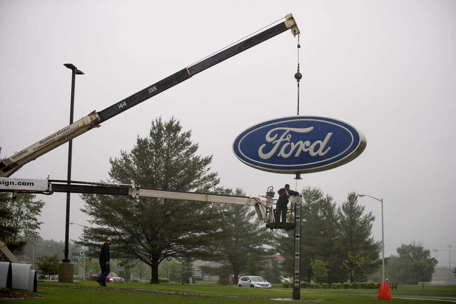 The sign from Midland Ford-Lincoln is moved to its new location on Joe Mann Boulevard by Higher Image Design. Photo: Neil Blake | Nblake@mdn.net