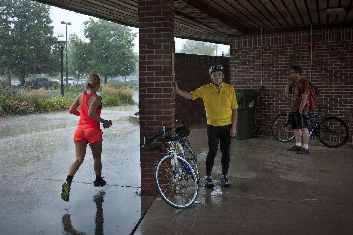 """Jasmine Ortmann, left, of Midland runs circle around the farmers market awning while Tom Young of Auburn and Jason Booth of Midland wait for the rain to subside Thursday morning. """"I was trying to get in 12 miles today,"""" Ortmann, who is training for the Detroit marathon said. """"People warned by about the rain."""""""