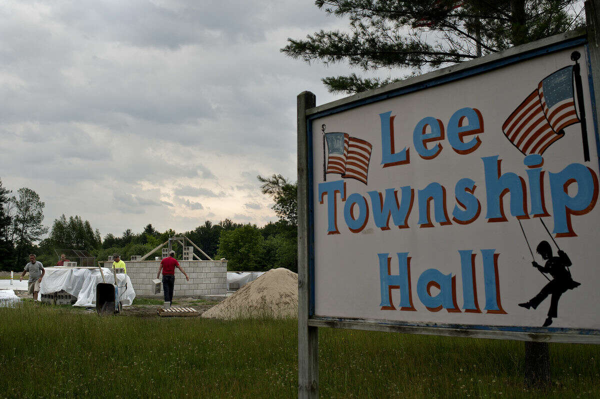 Workers from JBS Contracting and Roger Fussman Concrete and Masonry pack for the day before storms hit at the site of the Lee Township Hall on Monday.