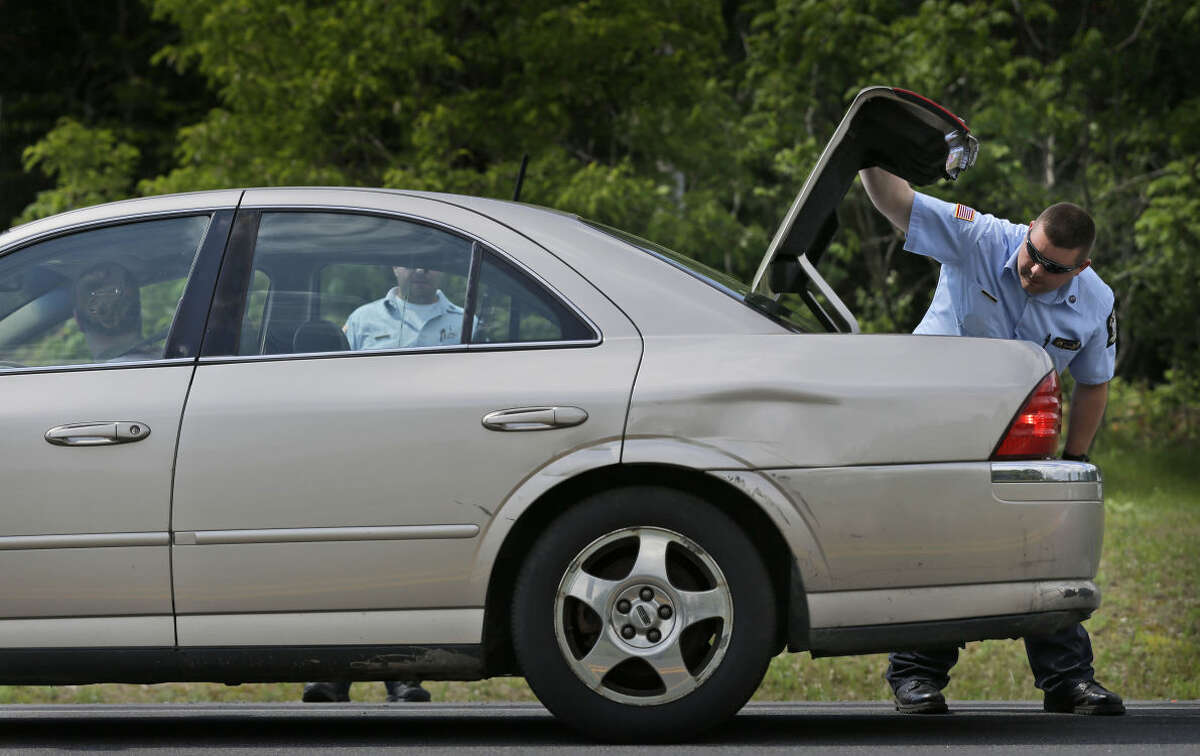 Law enforcement officials check the trunk of a car at a check point near the border of Dannemora, N.Y., Wednesday, June 10, 2015. Police were resuming house-to-house searches near the maximum-security prison in northern New York where David Sweat and Richard Matt , two killers escaped using power tools.