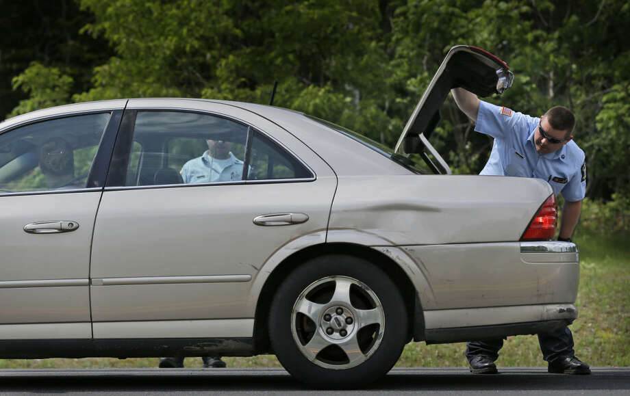 Law enforcement officials check the trunk of a car at a check point near the border of Dannemora, N.Y., Wednesday, June 10, 2015. Police were resuming house-to-house searches near the maximum-security prison in northern New York where David Sweat and Richard Matt , two killers escaped using power tools. Photo: Seth Wenig