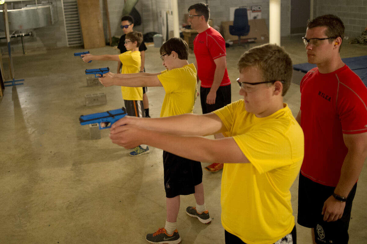 BRITTNEY LOHMILLER | blohmiller@mdn.net From left: Midland Police Department intern Adrianna Mysliwski of Bay City watches Caleb Belgiorno, 14, of Homer Township shot at the target while Officer Dan Keeler watches David Burlingame, 13, of Mills Township take aim and Deputy Brad Staley watches Brandon Thomas, 13, of Ingersoll Township prepare to shoot during the Midland County Youth Law Enforcement Academy Wednesday afternoon at the Midland Law Enforcement Center.. This is the first year students were allowed to participate in the shooting range during the the week-long program. The simulation guns shot dyed blue wax bullets.