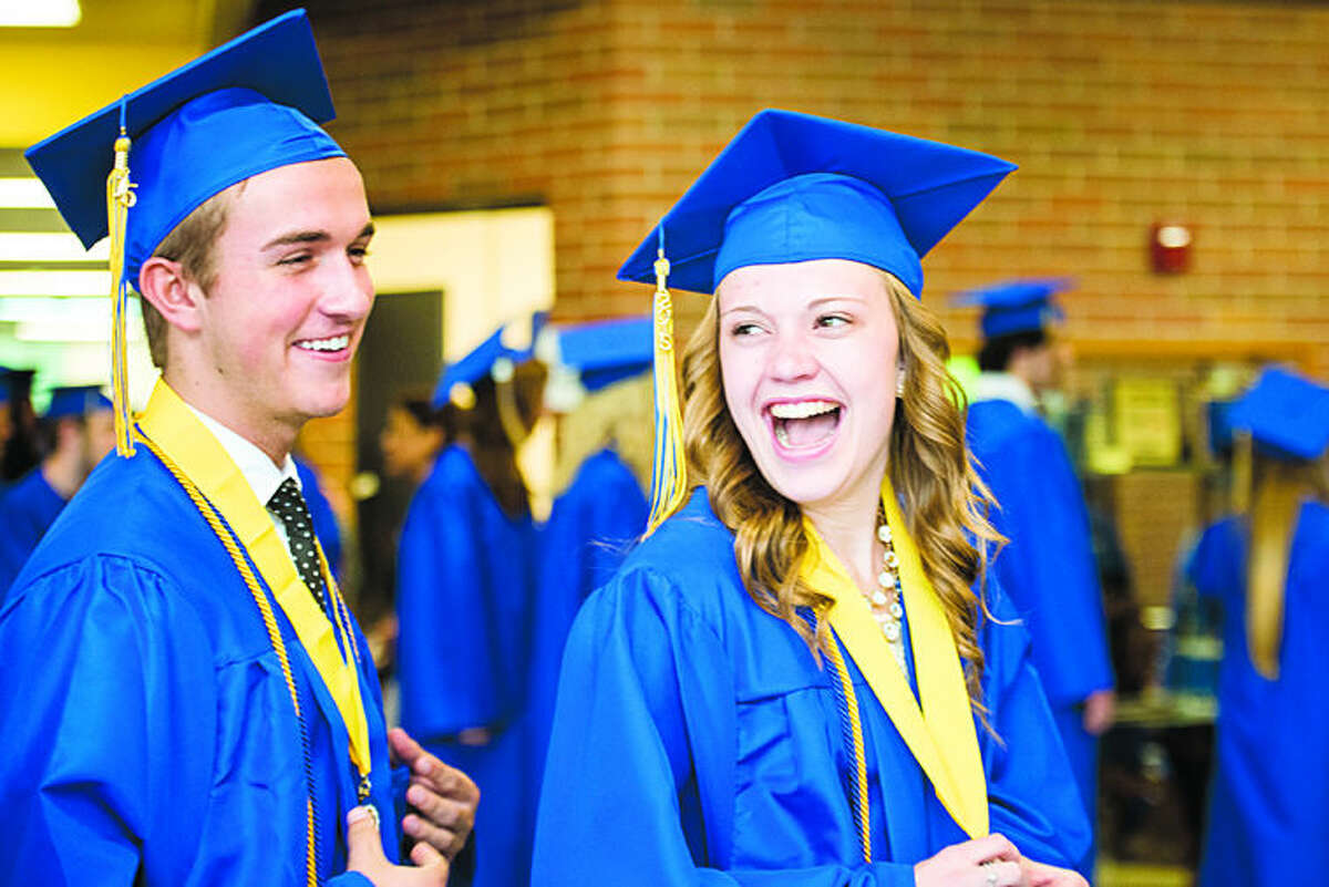 Graduates Blake Groulx and Sydney Gross laugh as they make their way to the gymnasium at the Midland High School commencement ceremony for the Class of 2015 on Friday.