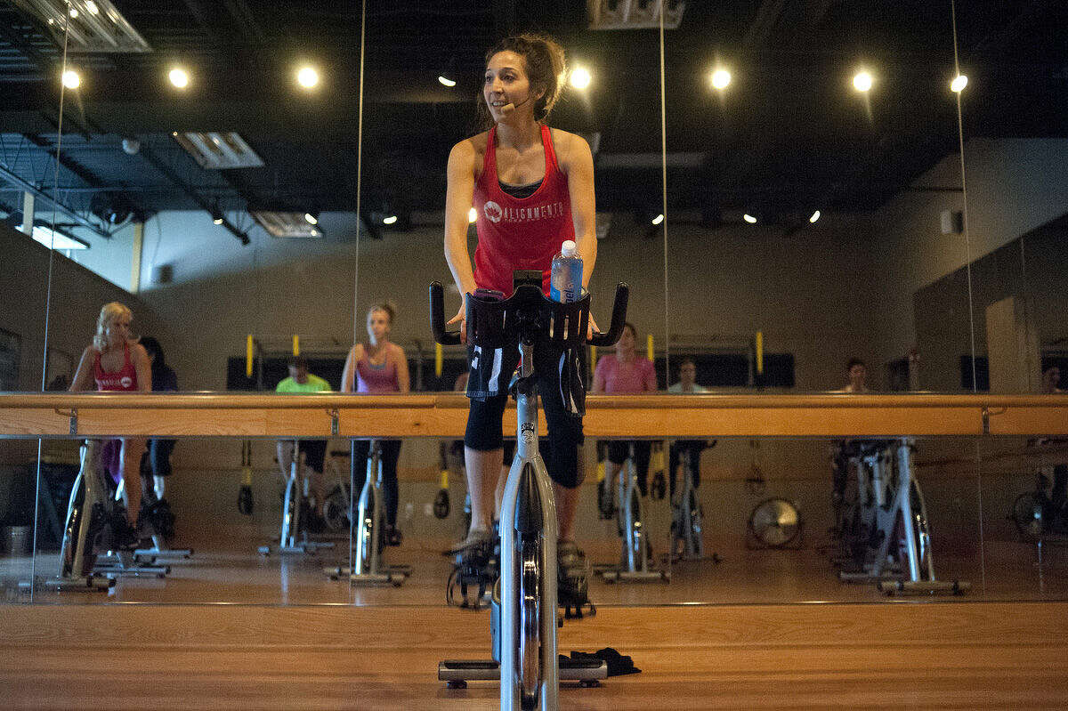Keri Kenney teaches a cycling class at Alignment 8 Yoga and Cycle Friday morning. Keri and her husband, James Kenney, took over Alignment 8 on March of this year.