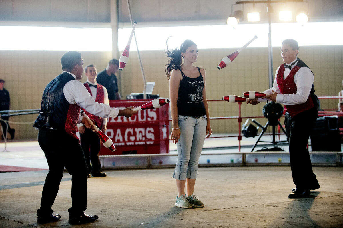 Kendra Couture of Harrison holds still as Juan Earhart, left, and James Earhart, right, juggle around her during the Circus Pages circus at the Midland County Fairgrounds on Thursday.