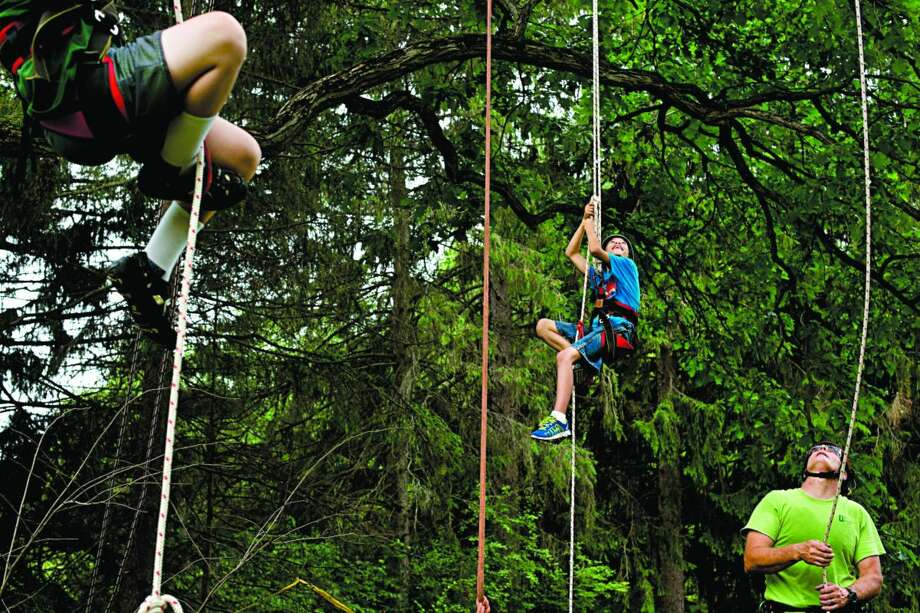 """BRITTNEY LOHMILLER   blohmiller@mdn.net From left: 9-year-old Ian Arnold and 9-year-old Brandon Christenson both of Midland pull themselves up on ropes to climb the oak tree in Whiting Forest while Dow Gardens arborist Ray Jennings talks to Josh Kline, 12, of Midland about how to descend using the rope Thursday morning. This is the first year that Dow Gardens is offering a recreational tree climbing class. Climbers are belted into a harness and use a rope and pulley system to shimmy their way up the tree. """"Mike Whiting wanted to see kids up in the trees,"""" Jennings said. """"because that's what he and his brother did growing up so he helped get this program started."""" Photo: Brittney Lohmiller/Midland Daily News"""
