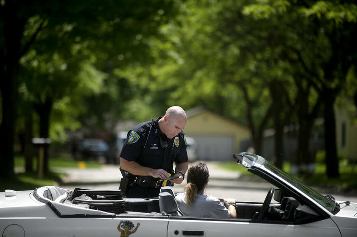 Midland Police Officer Paul McDonald talks with a driver he pulled over for speeding Wednesday afternoon.