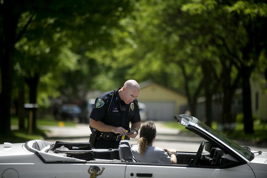 Midland Police Officer Paul McDonald talks with a driver he pulled over for speeding Wednesday afternoon. Photo: Brittney Lohmiller | Blohmiller@mdn.net