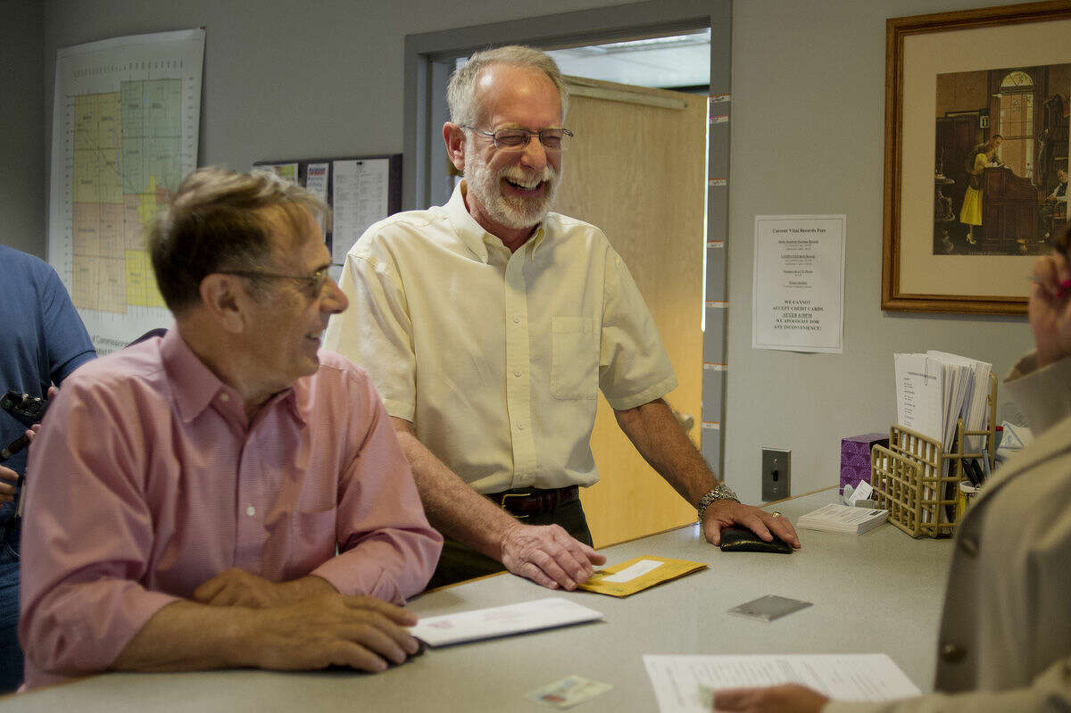"""Alan Harrow, 72, left, and Douglas Webster, 64, apply for their marriage license on Friday after the U.S. Supreme Court ruled 5-4 to allow same sex marriage in the United States. """"Not bad for a 20-year engagement,"""" Webster said."""