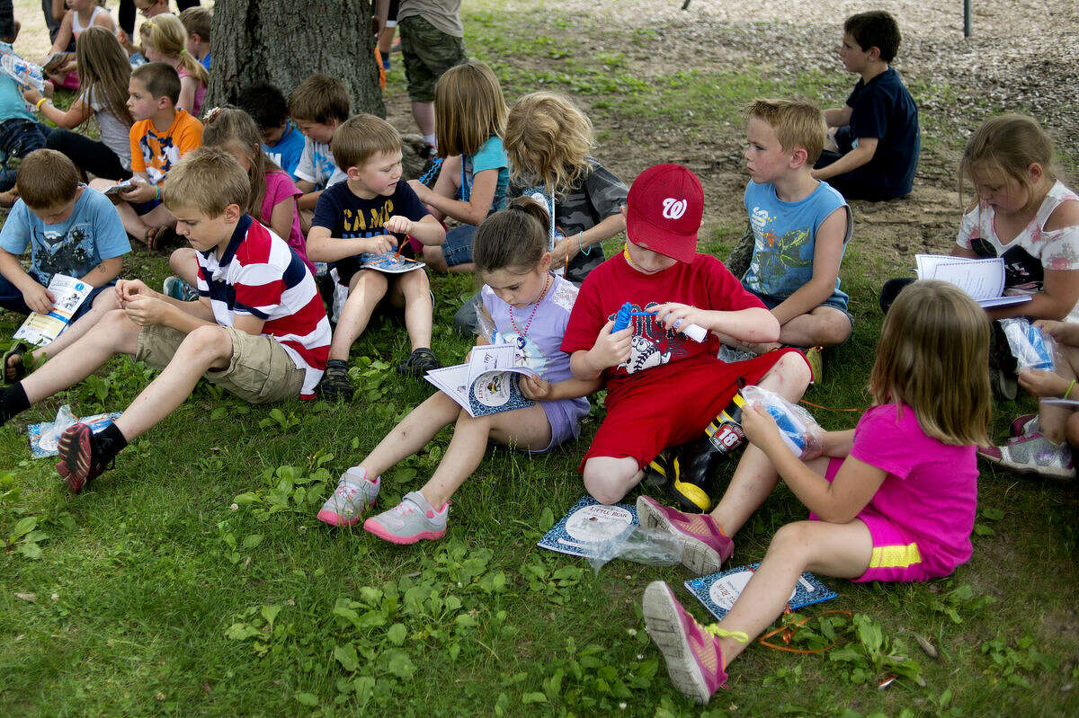"""Floyd Elementary School day campers look over their gift packet from Young Leaders United on Thursday. Inside the packet was the book """"Little Bear"""" by Else Holmelund Minarik and a jump rope. United Way volunteers were at the school installing a Born Learning Trail and a Little Free Library."""