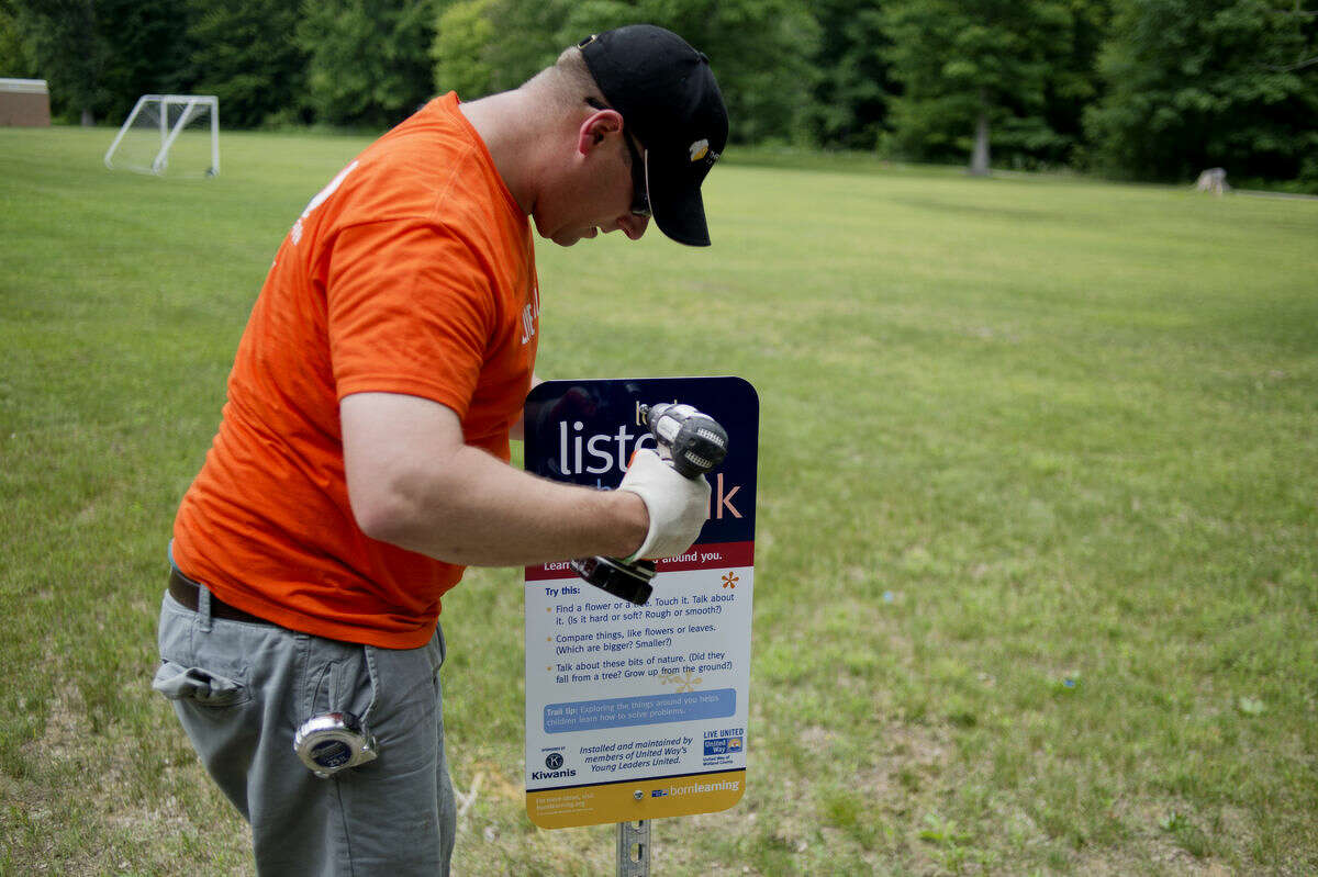 United Way volunteer Joel Keister, a Three Rivers employee, installs a sign along the Born Learning Trail at Floyd Elementary on Thursday. The trail has learning games and exercises that promote physical activity.