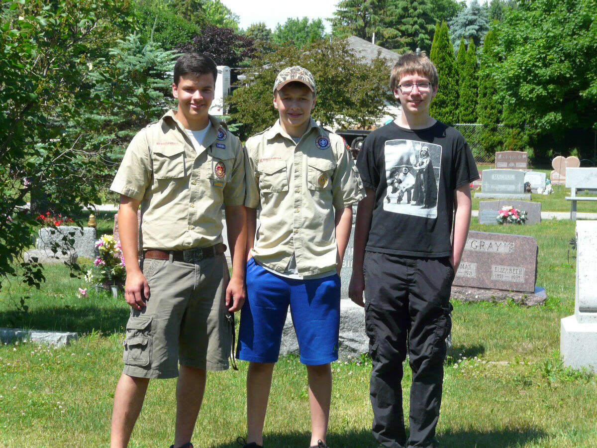 Jacob Gudmundsen, 17, left, poses with his brother, Javin Gudmundsen, 14, center, and Nathan Herzog, also 14. Nathan and Javin were among the family and friends who turned out to help Jacob work on an Eagle Scout service project that entailed photographing more than 1,600 grave markers for a genealogical website.