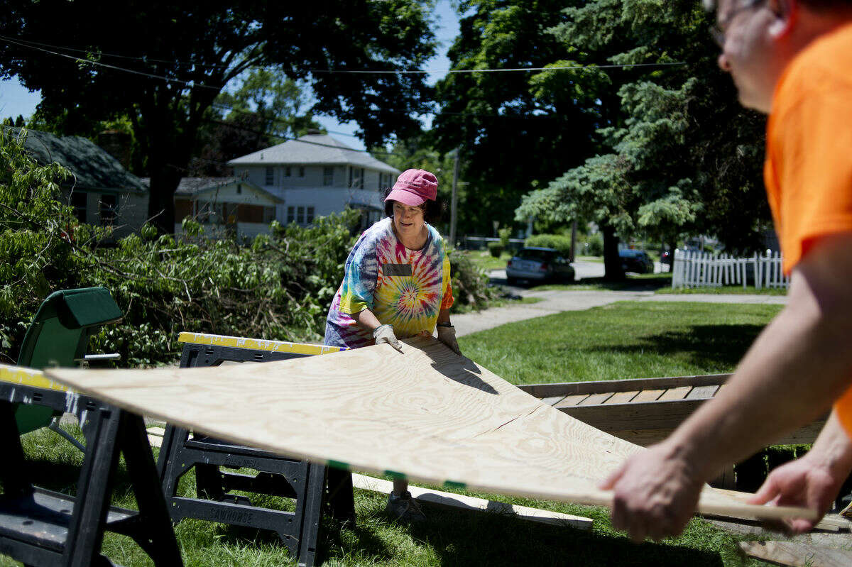 """Kim Steinke and the Rev. Roger Pancost, both of Midland, move a sheet of wood as they work on the home of Connie Kincaid in Saginaw on Tuesday. Volunteers from United Church of Christ in Midland worked on Kincaid's home doing repairs to the porch as well as tackling yardwork. """"There were weeds taller than me,"""" Kincaid said about her yard. Kincaid is in a motorized wheelchair and appreciated the help."""