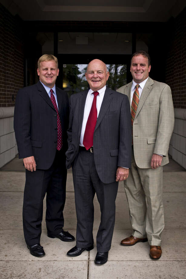 Ieuter Insurance Group president and co-owner Cal Ieuter, center, is pictured with his sons and fellow co-owners, Karl Ieuter, left, and Kurt Ieuter, right, on Wednesday at the Ieuter Insurance Group in Midland. The insurance agency is celebrating its 75th year in business. Photo: Erin Kirkland | Midland Daily News