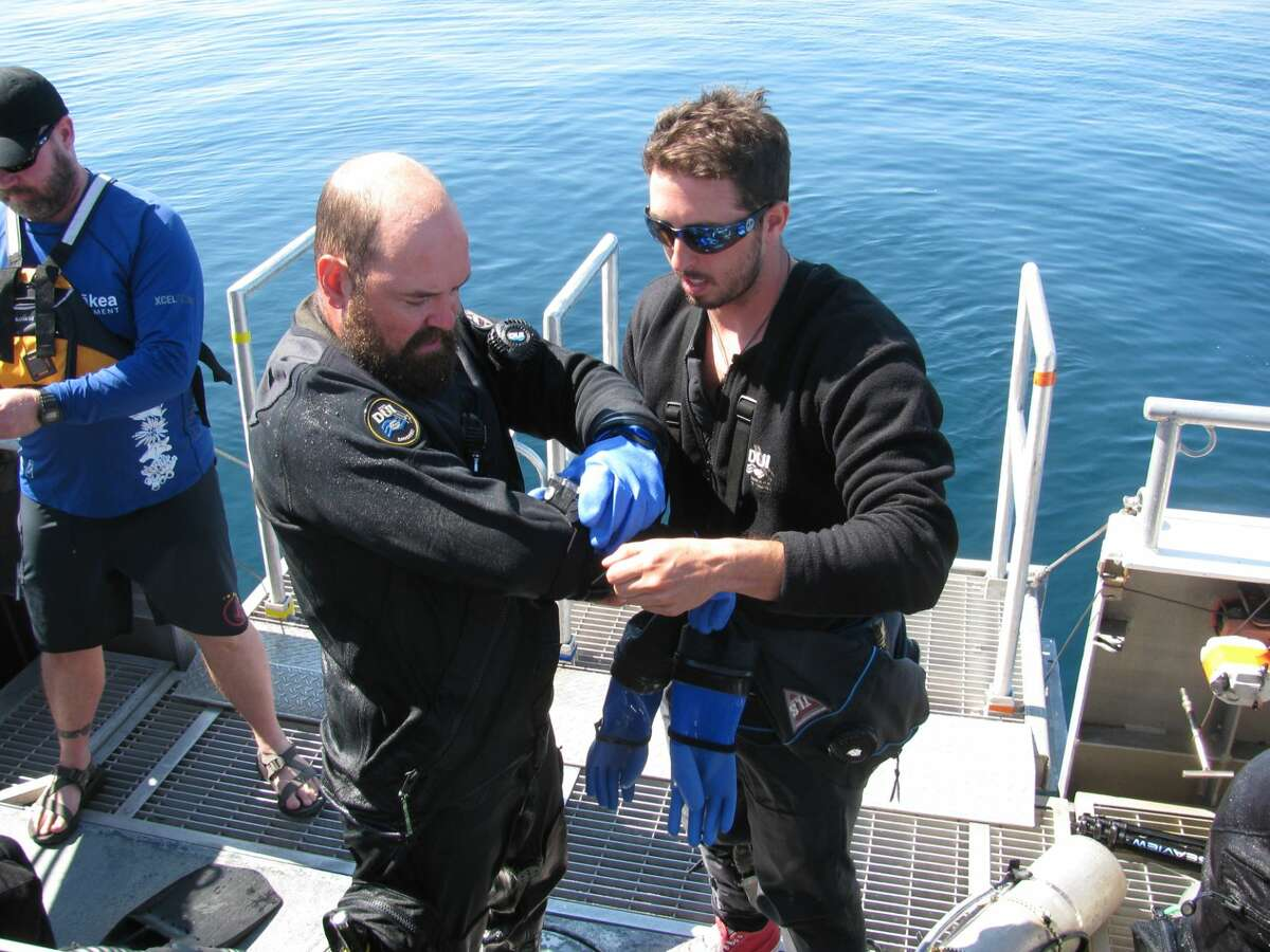 In a July 22, 2015 photo, National Oceanic and Atmospheric Administration (NOAA) diver Joe Hoyt, left, puts on his gear with the help of support diver Jeremy Borrelli before diving to the shipwreck Defiance in Lake Huron near Presque Isle, Mich. The Defiance, a well-preserved schooner that sunk in 1854, is one of the earliest wrecks in the Thunder Bay National Marine Sanctuary, and Hoyt is using photographic and imaging technology to rapidly and accurately create 3-D models of the Defiance and other wrecks.