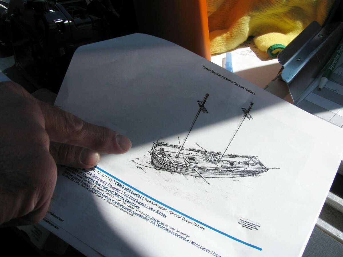 In a July 22, 2015 photo, Russ Green, deputy superintendent and research coordinator at the Thunder Bay National Marine Sanctuary, looks over a rendering of the shipwreck Defiance before diving to it in Lake Huron, near Presque Isle, Mich. Green's team is using photographic and imaging technology to rapidly and accurately create 3-D models and 360-degree views of the many shipwrecks resting far below the surface. The Defiance, a well-preserved schooner that sunk in 1854, is one of the earliest wrecks in the Thunder Bay National Marine Sanctuary.