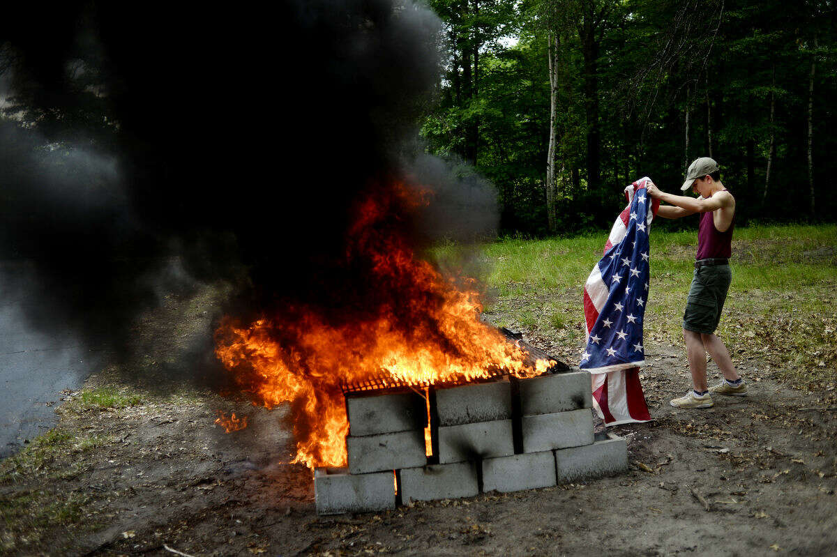 Nick Norris, 13, a Boy Scout from Troop 767, prepares to lay on old flag onto the fire during an American flag retirement ceremony on Sunday at the American Legion Berryhill Post 165.