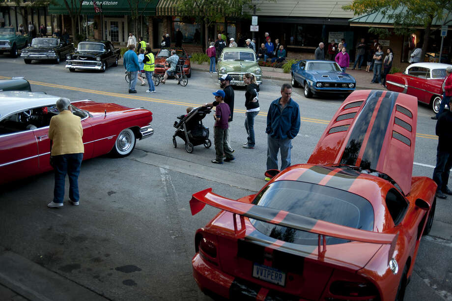 People walk up and down Main Street to take a look at hot rods, street cars, custom cars, antiques and motorcycles during the 26th annual Midland Downtown Business Association Cruise 'n Car Show Friday evening. Photo: Brittney Lohmiller | Midland Daily News