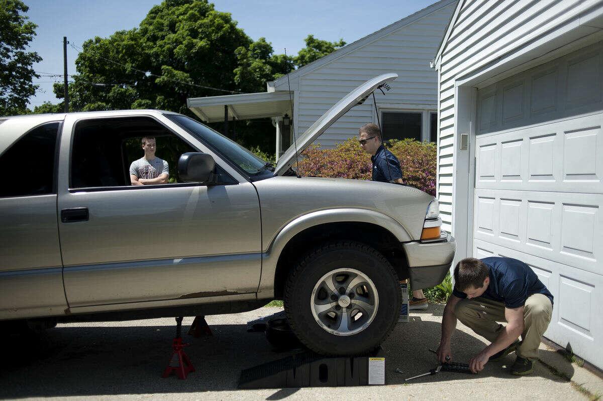 From left, Tyler Sanford watches Chandler Zablocki and Trevor Zablocki change the oil in his Chevy Blazer Wednesday afternoon.