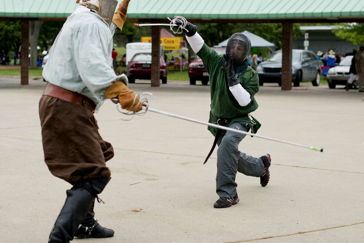 """Jonas """"Vigfus"""" Alooh of Saginaw, right, lunges for Rich Marshall of Midland as they practice renaissance rapier fencing on Thursday near the Tridge in Midland. They use combat rules from the Society for Creative Anachronism, a living history group, and practice near the Tridge every other Thursday. """"In the sixteenth century if you were stabbed in the core, you would die within weeks,"""" Marshall said while going over what constituted a """"kill shot."""" The group invites anyone over 18 to borrow gear and give it a try for free. For more information contact Rich Marshall at mrkayack@yahoo.com."""