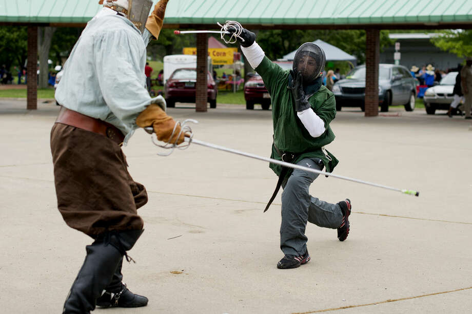 "Jonas ""Vigfus"" Alooh of Saginaw, right, lunges for Rich Marshall of Midland as they practice renaissance rapier fencing on Thursday near the Tridge in Midland. They use combat rules from the Society for Creative Anachronism, a living history group, and practice near the Tridge every other Thursday. ""In the sixteenth century if you were stabbed in the core, you would die within weeks,"" Marshall said while going over what constituted a ""kill shot."" The group invites anyone over 18 to borrow gear and give it a try for free. For more information contact Rich Marshall at mrkayack@yahoo.com. Photo: Neil Blake/Midland Daily News"