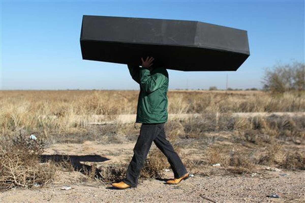 Un manifestante carga un ataúd falso en representación de los migrantes que han fallecido, durante una protesta afuera del centro de detención del Servicio de Control de Inmigración y Aduanas de Estados Unidos (ICE) , en Eloy, Arizona, el 20 de enero de 2016. Grupos de derechos civiles reportaron el 25 de febrero de 2016 que años de atención médica inadecuada en centros de detenciones para migrantes en EEUU, han causado muertes de detenidos. (Foto AP/Ricardo Arduengo, Archivo)