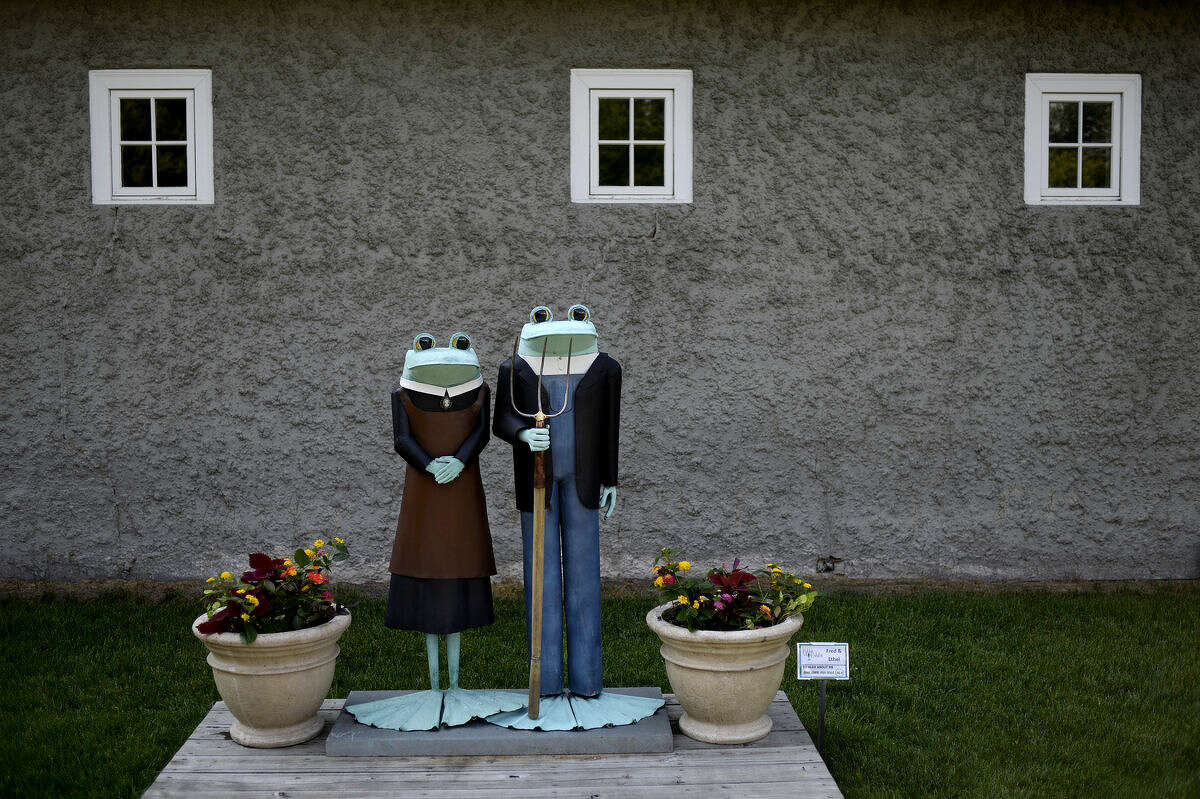 The sculpture titled 'Fred & Ethel' features a frog couple posed like the couple in the famous Grant Wood painting 'American Gothic' as part of Ribbit! the Exhibit on Monday at Dow Gardens. The frog-themed display features 20 characters crafted by artist J.A. Cobb. The exhibit is on display from June to August.