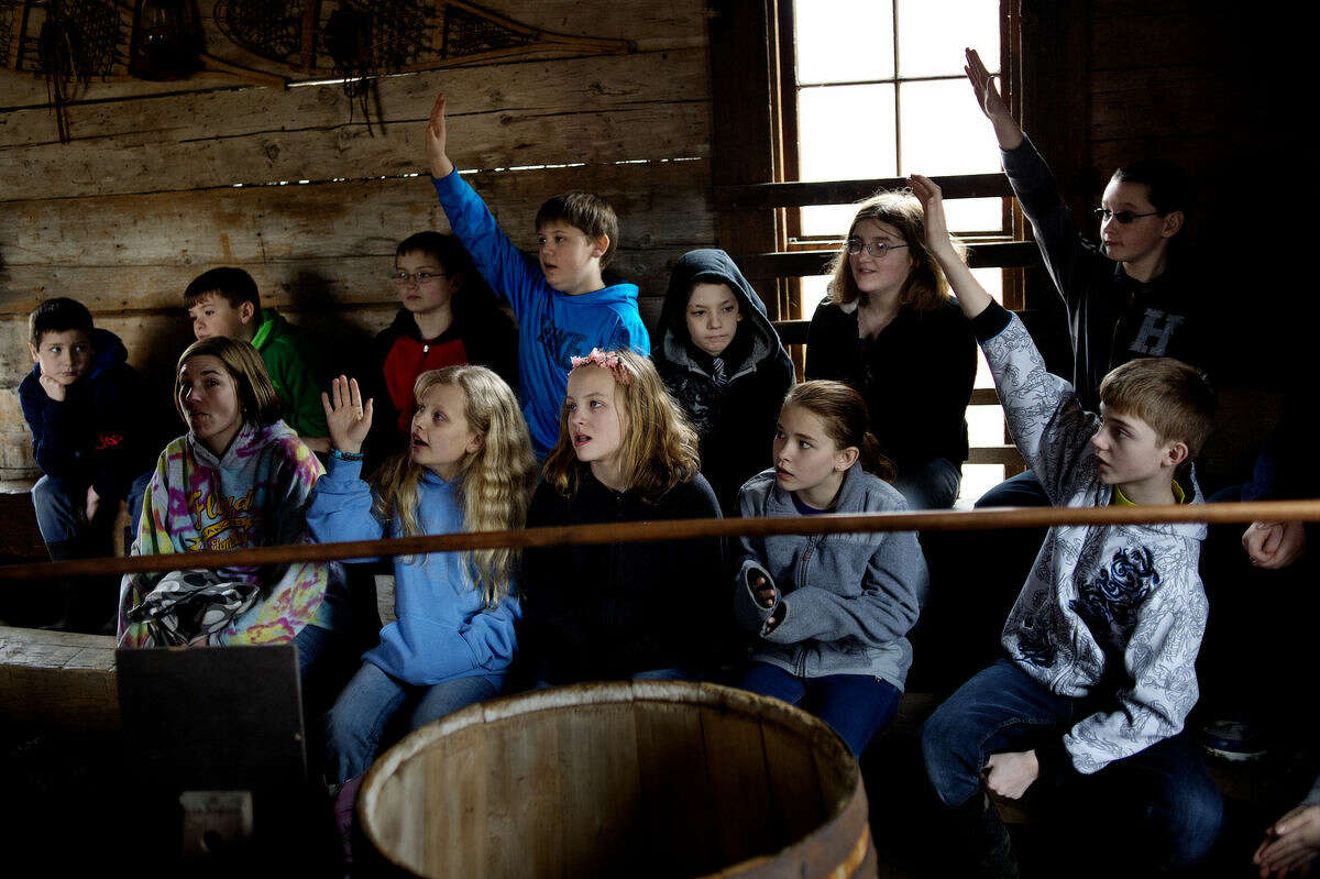 Floyd Elementary fifth-graders raise their hands while answering questions about the maple syrup making process on Monday in the sugarhouse at the Chippewa Nature Center.