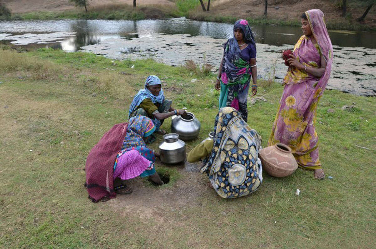 Prior to the Borewell project, women such as these had to walk sometimes up to three miles to a nearby river, dig a hole and wait for it to fill up with water to carry back to the village.