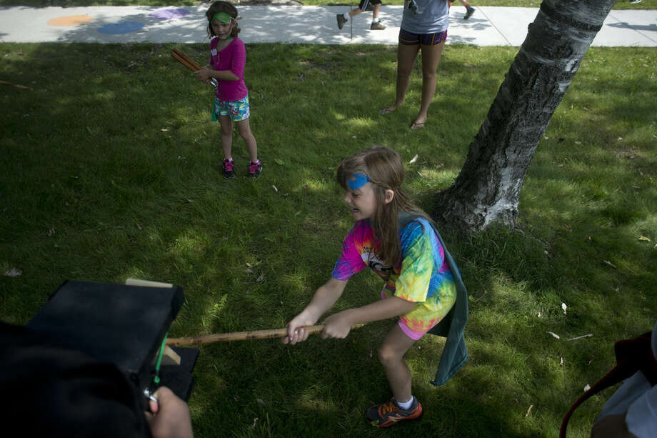 Eight-year-old Lillian Blohm of Midland breaks a wooden board held by Gateway Martial Arts' Nathan Edmonds, 14, during the Superhero Training Academy Wednesday afternoon at Plymouth Park. Superheroes in training made capes, worked on puzzles and learned how to break wooden boards as part of the free one-day academy offered by the Grace A. Dow Memorial Library and the Midland Parks and Recreations. Photo: Brittney Lohmiller | Blohmiller@mdn.net