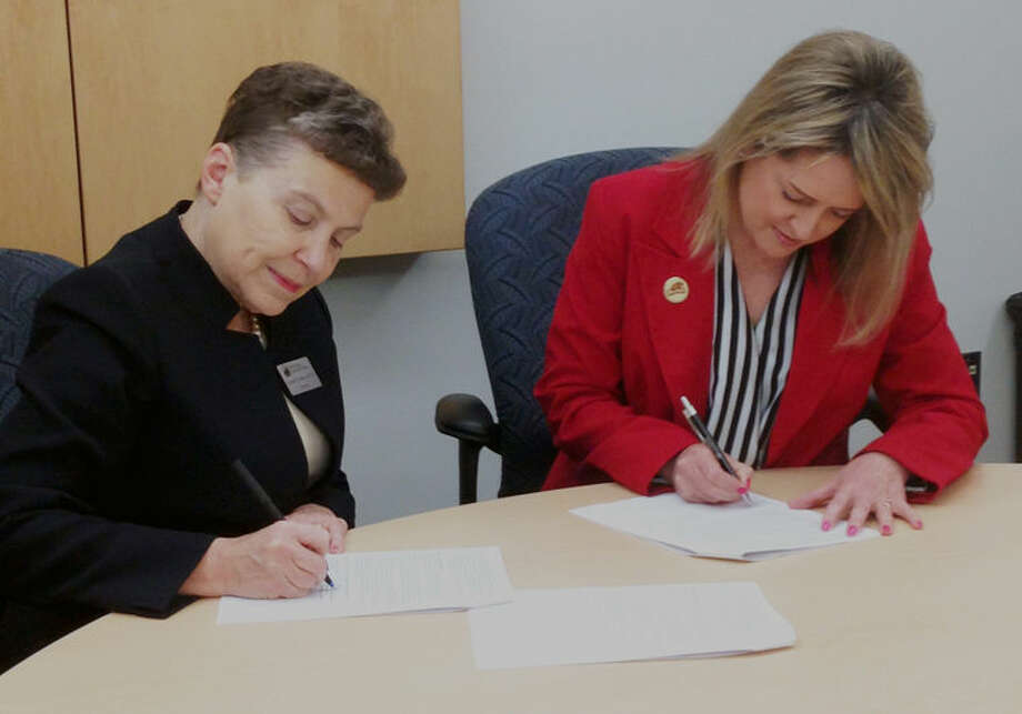Dr. Christine Hammond, Mid Michigan Community College president, and Susan Wooden, Beaverton Rural Schools superintendent, sign the State of Michigan application for the Early College Program. Photo: Photo Provided