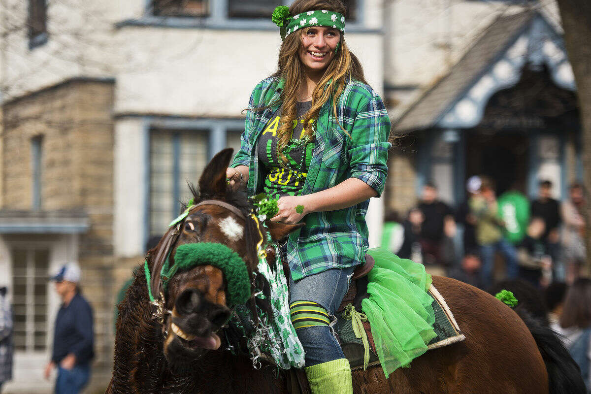 Samantha Morse of Bay City rides Thunder Lynn as the horse shakes her head during the Bay City St. Patrick's Day Parade on Sunday. Morse, who rode with the Humane Society of Bay County, said she spent about an hour readying Thunder Lynn for the parade, braiding her mane and adding beads, flowers and other green accents.