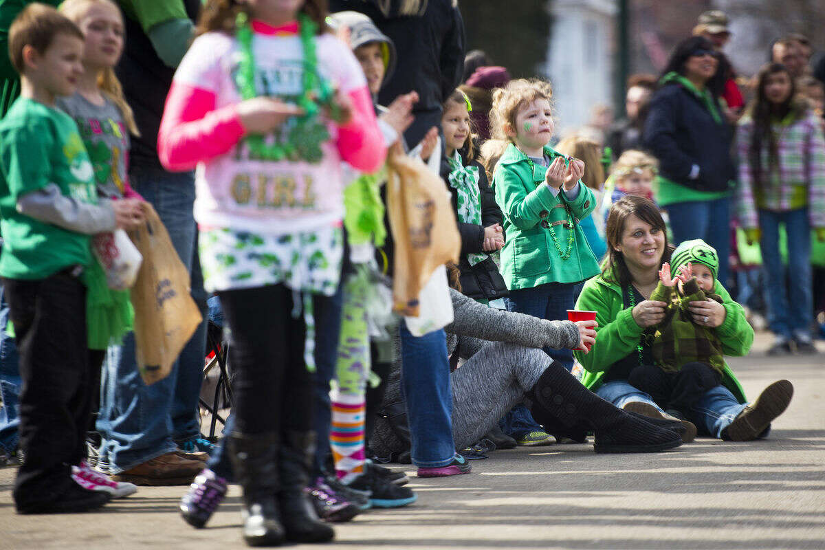 """Erica Ray, seated, right, and her son, Lincoln, listen to the Saginaw High Marching Band at the Bay City St. Patrick's Day Parade on Sunday. """"He's having a good time,"""" Ray said of Lincoln, who is 1 and a half. She added it was his first time attending the St. Patrick's Day Parade, since last year's temperatures were frigid and he was too young."""