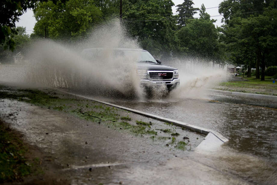 A GMC pickup splashes through standing water on Indian Street on Friday morning. Rain forced some street closures in Midland due to minor flooding. Photo: Neil Blake/Midland Daily News