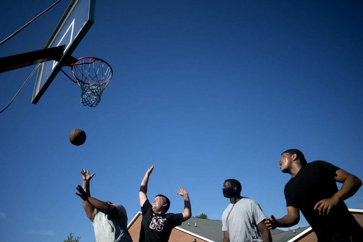 """From left: James Parmele of Midland, Keaton Kelly of Midland, Chad Crawford of Midland and Collin Jones of Midland play a game of two on two at the Midland Baptist Church's parking lot Tuesday afternoon. """"It's nice weather,"""" Parmele said. """"I got out of work early and wanted to get some exercise too."""" Parmele, Kelly and Crawford all played football together when they attended H.H. Dow High School, Jones played golf."""