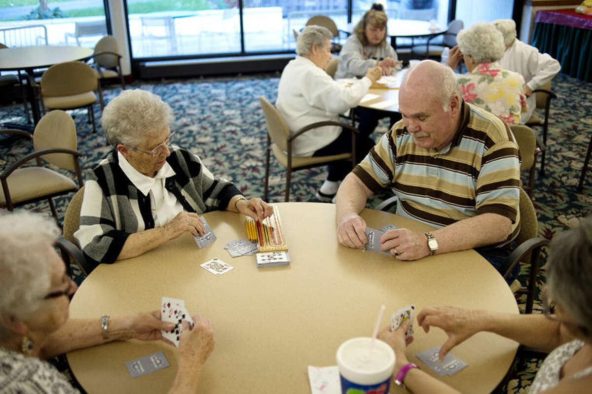 From left, Ruth Emerson, Donna McKinnon, Steve Yascolt and Bobbie Berthume play cribbage in the dining room at Washington Woods.