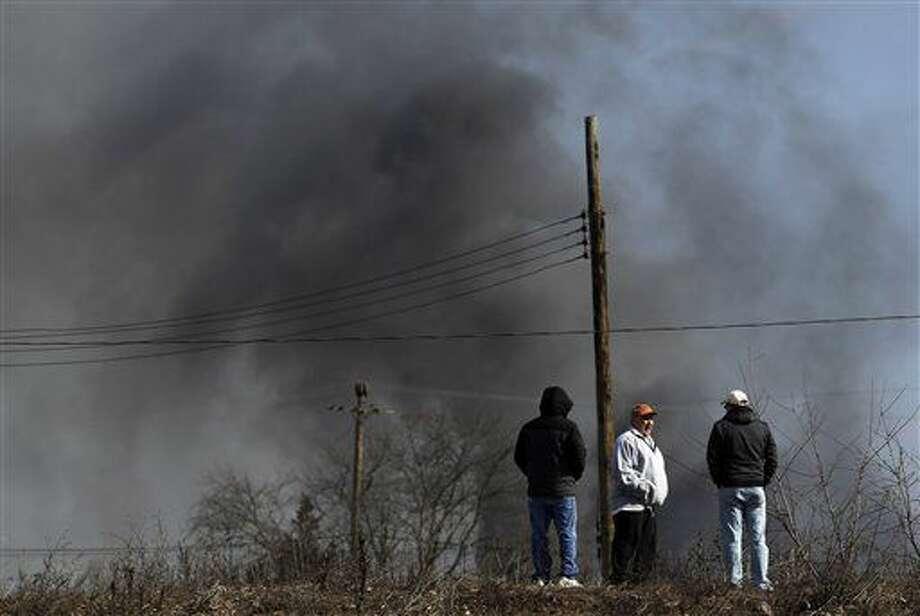 John Adams, izquierda, Tommy DeStefano, al centro, y Dave Ellmer conversan en una colina desde donde se puede ver un incendio en una bodega, un día después de que las flamas engulleron la instalación, el viernes 12 de febrero de 2016, en Hillsborough, New Jersey. Los bomberos contuvieron el incendio y funcionarios dijeron que no representó un riesgo para la salud pública. (Foto AP/Julio Cortez) Photo: Julio Cortez